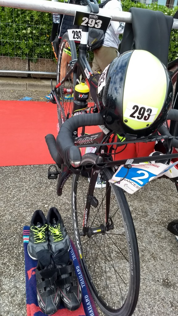 Placing the helmet on the handlebars makes it easier to remember. Races are strict about wearing and securing the helmet on your head when handling the bike in transition, if you forget you might get a time penalty!